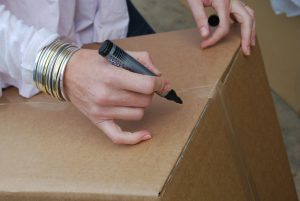 person writing on a box
